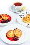 Food of Crepes, cheesecakes with berry sause and cup of tee. Royalty Free Stock Photography