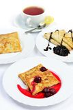 Food of Crepes, cheesecakes with berry sause and cup of tee. Royalty Free Stock Photo