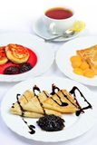 Food with Crepes, cheesecakes and cup of tee. Royalty Free Stock Photography