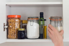 Food cupboard, pantry with jars, hand. Stocked kitchen pantry with food - jars and containers of cereals, jam, coffee, sugar, flour, oil, vinegar, rice stock photos