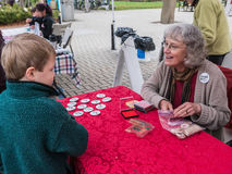 Food Day workers hands farmers market tokens to young boy Stock Photos