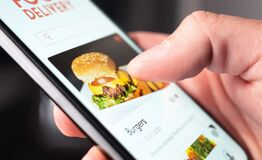 Food delivery app order with phone. Online mobile service for take away burger and pizza. Hungry man reading restaurant menu.