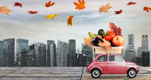 Autumn food delivery. Food delivery. Autumn red toy car with fallen leaves delivering fruits and vegetables against business district buildings Stock Photography