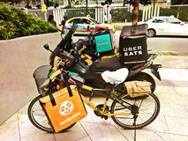 Food delivery bikes. Bicycle and motorcycles representing food delivery companies in Singapore - FoodPanda, Uber Eats and Deliveroo stock image