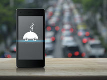 Food delivery concept. Restaurant cloche flat icon on modern smart phone screen on wooden table over blur of rush hour with cars and road, Food delivery concept Royalty Free Stock Images