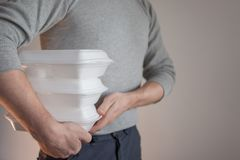Food delivery. The courier man holding a container of food. stock image