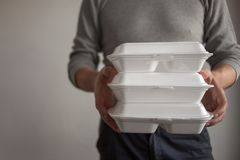Food delivery. The courier man holding a container of food. royalty free stock photography