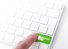 Food delivery. Finger pressing a green key labeled delivery with fast food symbol on a computer keyboard, concept for e-commerce food delivery service royalty free stock photos