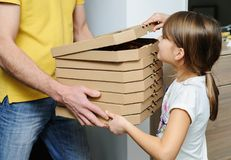 Food delivery home. The man is holding boxes with pizzas. The girl is looking into the top box Stock Photo