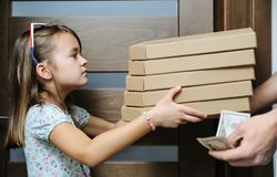 Food delivery home. The girl is taking boxes from the pizza deliverer Royalty Free Stock Photography