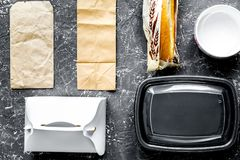 Food delivery with paper bags and sandwich on gray background to. Food delivery service workdesk with paper bags and sandwich on gray background top view royalty free stock photography