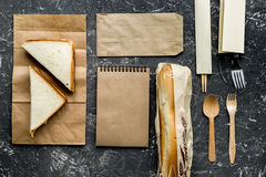 Food delivery with paper bags and sandwich gray background top view mock-up. Food delivery service workdesk with paper bags and sandwich on gray background top royalty free stock photos