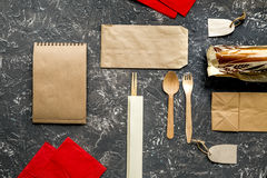 Food delivery with paper bags and sandwich on gray background top view mockup. Food delivery service workdesk with paper bags, flatware and sandwich on gray stock photography