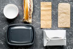 Food delivery with paper bags and sandwich on gray background top view. Food delivery service workdesk with paper bags and sandwich on gray background top view stock image
