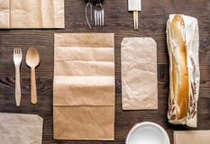 Food delivery with paper bags and sandwich top view mock up. Food delivery service workdesk with paper bags and sandwich on wooden background top view mock up royalty free stock image