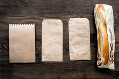 Food delivery with paper bags and sandwich top view space for text. Food delivery service workdesk with paper bags and sandwich on wooden background top view stock photos