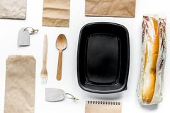 Food delivery with paper bags and sandwich on white background t. Food delivery service workdesk with paper bags and sandwich on white background top view royalty free stock photography