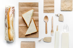 Food delivery with paper bags and sandwich white background top view mock-up. Food delivery service workdesk with paper bags and sandwich on white background top royalty free stock photos