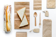 Food delivery with paper bags and sandwich on white background top view. Food delivery service workdesk with paper bags and sandwich on white background top view royalty free stock photo