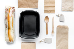 Food delivery with paper bags and sandwich on white background top view. Food delivery service workdesk with paper bags and sandwich on white background top view royalty free stock photography