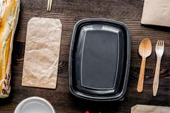 Food delivery with paper bags and sandwich on wooden background. Food delivery service workdesk with paper bags and sandwich on wooden background top view royalty free stock photography