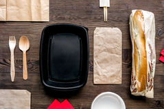 Food delivery with paper bags and sandwich on wooden background top view. Food delivery service workdesk with paper bags and sandwich on wooden background top royalty free stock photo