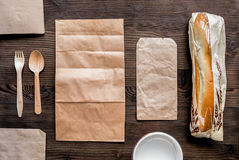 Food delivery with paper bags and sandwich on wooden background top view. Food delivery service workdesk with paper bags and sandwich on wooden background top royalty free stock image