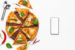 Food delivery. Pizza slices and smartphone with blank screen. On white background, top view stock photography