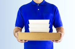 Food delivery service or order food online. Delivery man in blue. Uniform with hand holding food packaging container on the gray background. with clipping path royalty free stock photography