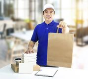 Food delivery service or order food online. Man holding paper ba. G and food packaging container with coffee cup on store background with copy space for text and stock photography