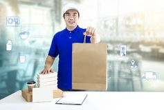 Food delivery service for order online and icon media. Delivery man in blue uniform hand holding paper bag, packaging container. And disposable cup for express royalty free stock photos