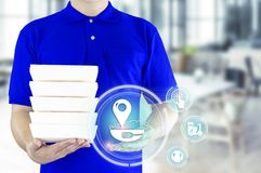 Food delivery service or order food online. Delivery man in blue uniform with hand holding fast food packaging container and icon. Media on the restaurant stock photography