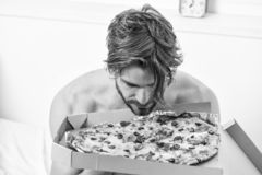 Food delivery service. Portrait of lazy muscular man eating pizza while laying on a bed at home. Man bearded handsome royalty free stock photos