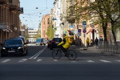 A food deliveryman in a yellow brand jacket rides a bicycle down the street Yandex food. St. Petersburg, Russia - May 04, 2019: a food deliveryman in a yellow royalty free stock photo