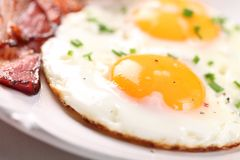Food detail. Close-up of fried egg and bacon on plate. Selective focus, shallow DOF royalty free stock images