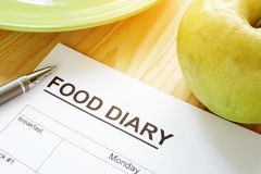 Food diary or meal plan and an apple. Food diary or meal plan and a green apple stock photo