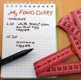 Food diary. Measuring tape, a marker and a notepad with a food diary Stock Photo