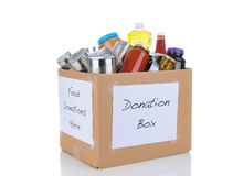 Food Donation Box. A box full of canned and packaged foods for a charity food donation drive. On white with reflection royalty free stock photo