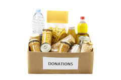 Food in a donation box. Food in a donation cardboard box, isolated in a white background royalty free stock photos