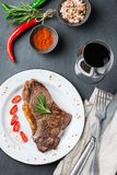 Grilled beef steak with spices ready for dinner. Food and drink concept. Grilled beef steak with spices ready for dinner on a dark table background. Flat lay top Stock Image