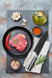 Raw beef steak with spices ready for cooking dinner. Food and drink concept. Raw beef steak with spices ready for cooking dinner on a dark table background. Flat Stock Photography