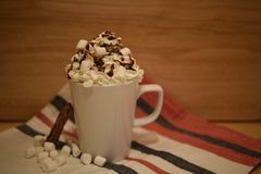 Close up food photography image of a hot chocolate drink in a mug with cream sauce and marshmallows on a red cloth background Royalty Free Stock Images