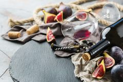 Bottle, corkscrew, glass of red wine, figs on a table Royalty Free Stock Photography