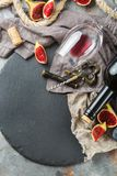 Bottle, corkscrew, glass of red wine, figs on a table Royalty Free Stock Photo