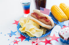 Food and drinks on american independence day party. National holidays, celebration, food and patriotism concept - close up of hot dog with american flag Stock Image