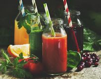 Food and drinks, selection of vegetable and fruit juices and smoothies in glass bottles with ingredients, set on rustic wooden. Table, selective  focus stock photo