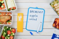 Food and dry erase board. Dry erase board with food list and a marker on the wooden surface. Plastic cutlery, tomato and lettuce salad, fish, a vegetable roll royalty free stock images