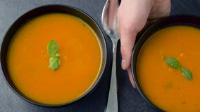 Hands putting bowl of pumpkin cream soup on table. Food, eating and new nordic cuisine concept - close up of hands putting second bowl of pumpkin cream soup on stock video