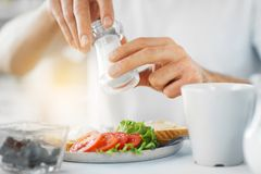 Close up of male hands seasoning food by salt mill stock photo
