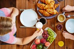 Woman with cream and coffee having breakfast Stock Image